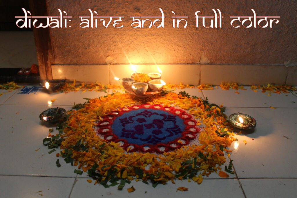 A rangoli for Diwali with candles and colored sand.