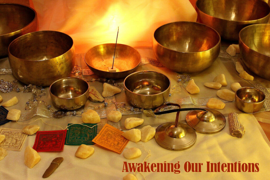 Tibetan singing bowls, with stones, incense, meditation beads, and prayer cards against a candlelit background.