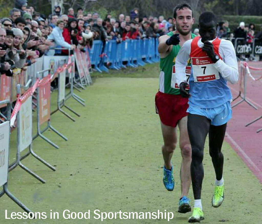 """Two athletes are near the finish line of a race. The runner in front has stopped and looks bewildered, while the runner behind him is pushing him forward and pointing him toward the finish line. The words """"Lessons in Good Sportsmanship"""" appear in the bottom left hand corner of the photo."""
