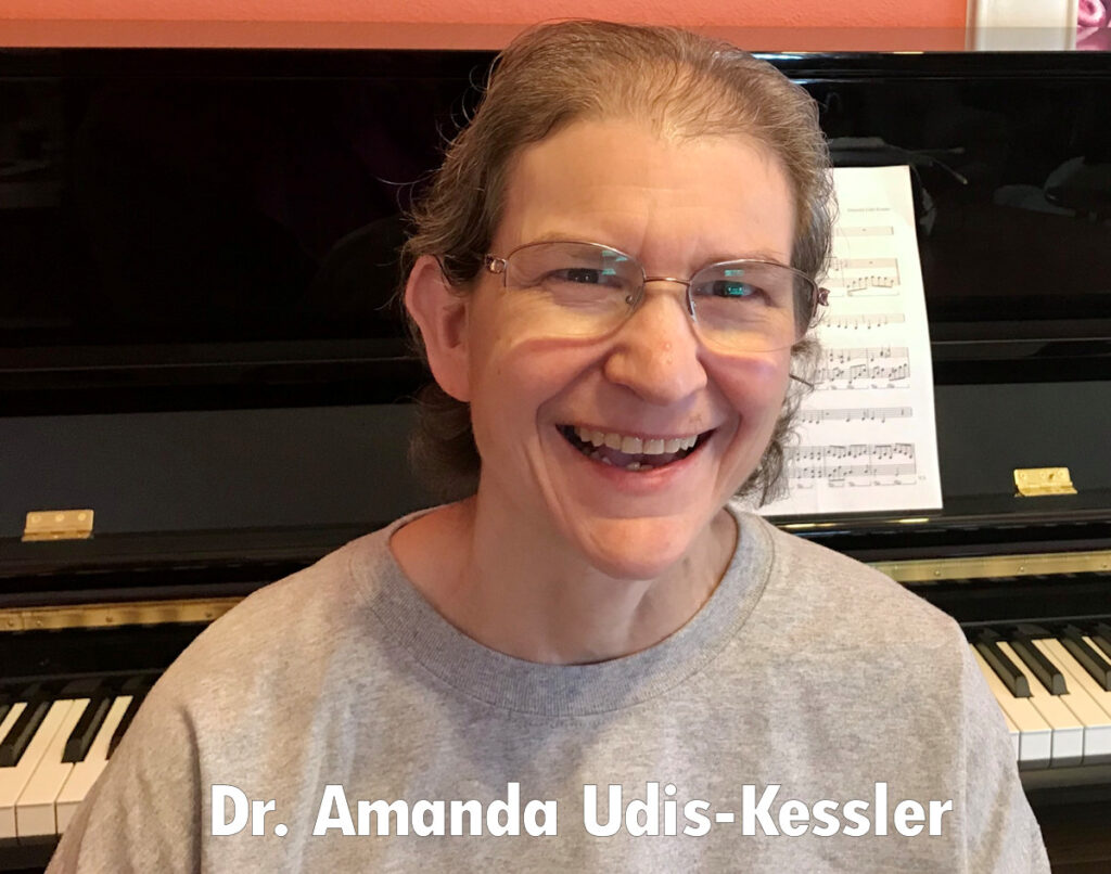 An image of Amanda Udis-Kessler smiling in front of a piano. Her hair is pulled back, and she is wearing a soft grey sweatshirt.