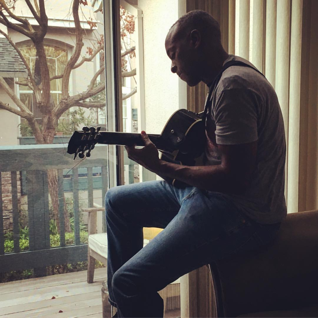 Photo of a man playing an acoustic guitar in front of a sliding glass door, looking out onto a balcony.